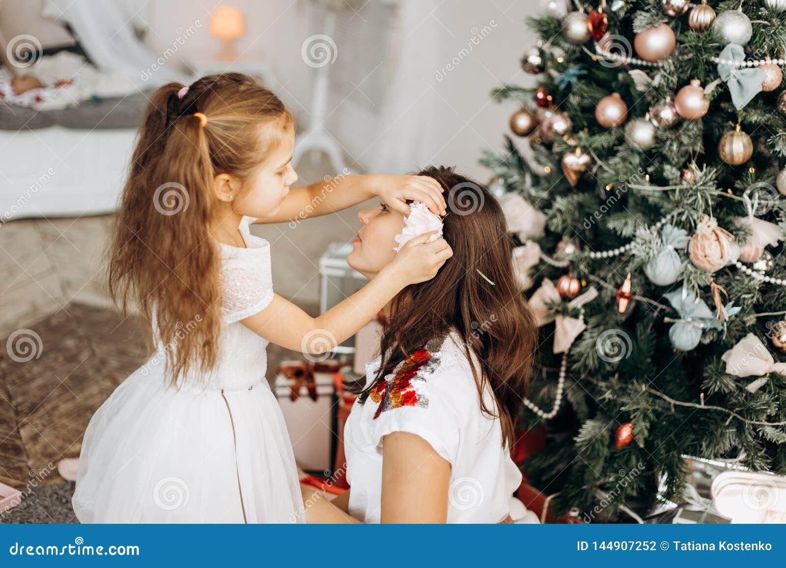 A filha pequena de encantamento no vestido agradável pôs uma flor no cabelo das mães perto da árvore de ano novo