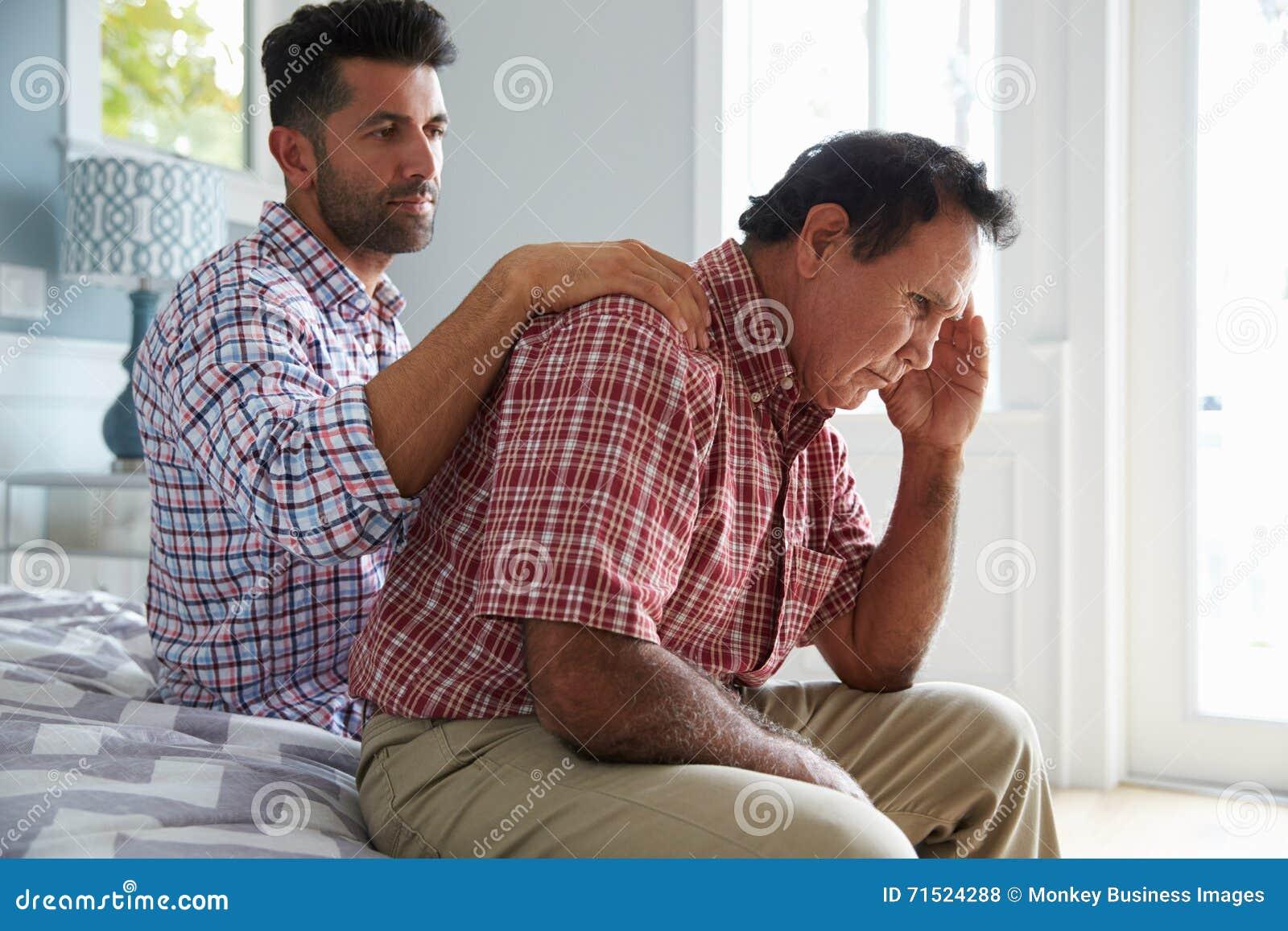 Filho adulto que consola o pai Suffering With Dementia