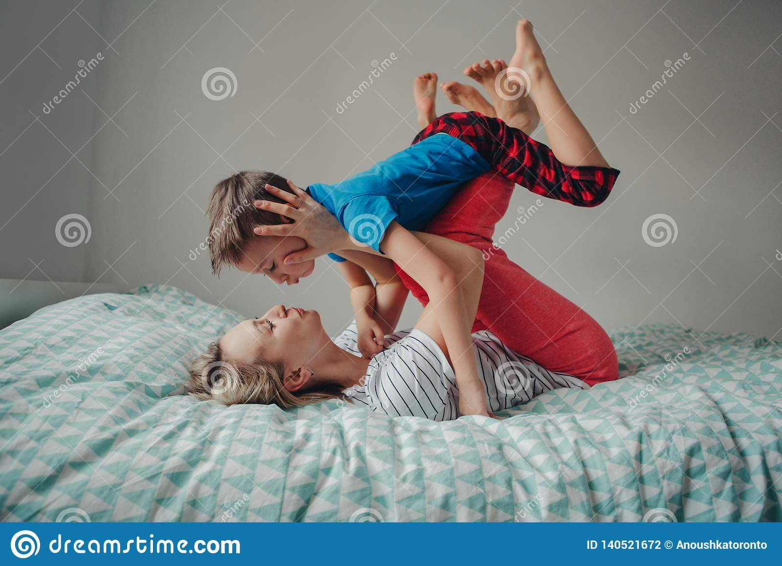 Filho caucasiano da mãe e do menino que joga junto no quarto em casa