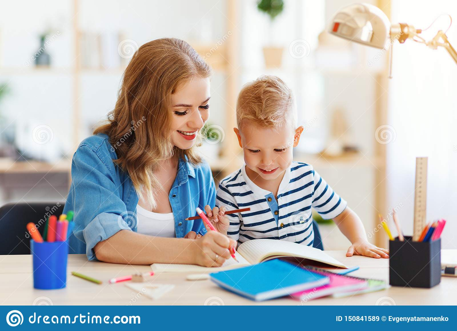 Filho da mãe e da criança que faz a escrita dos trabalhos de casa e que lê em casa