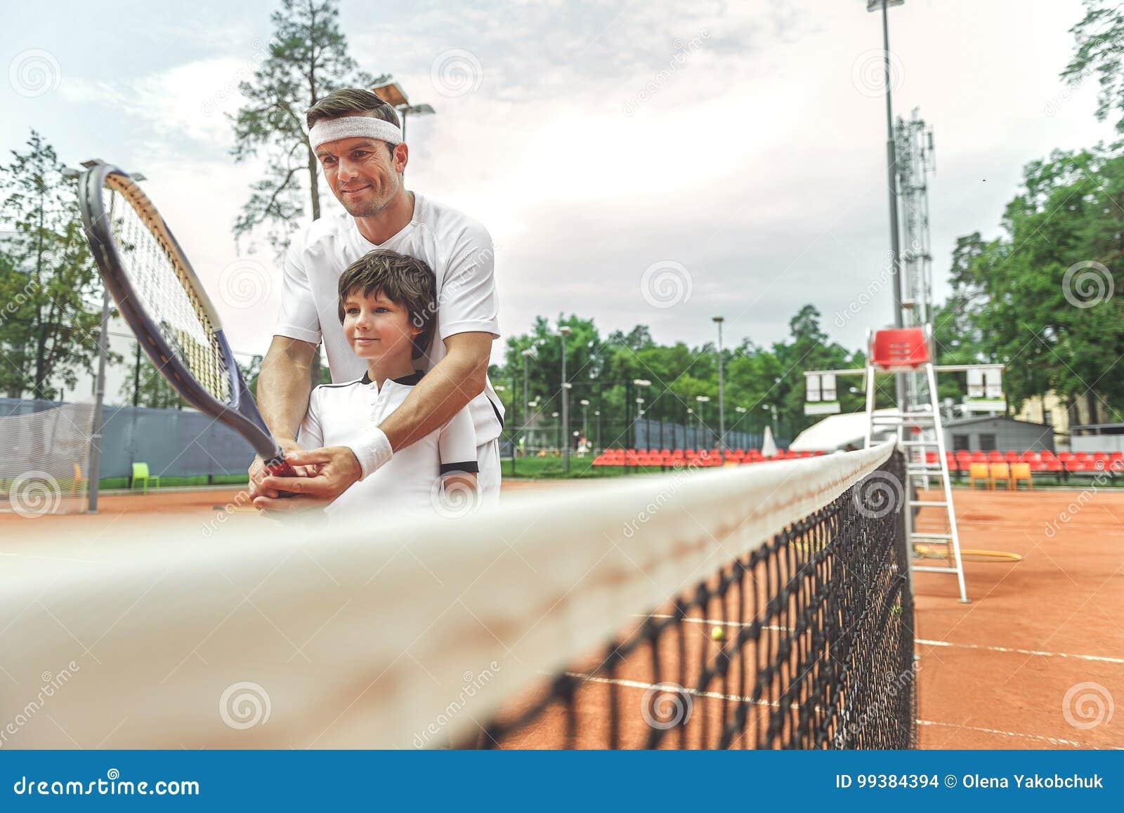 Filho de ensino do pai interessado para jogar o tênis