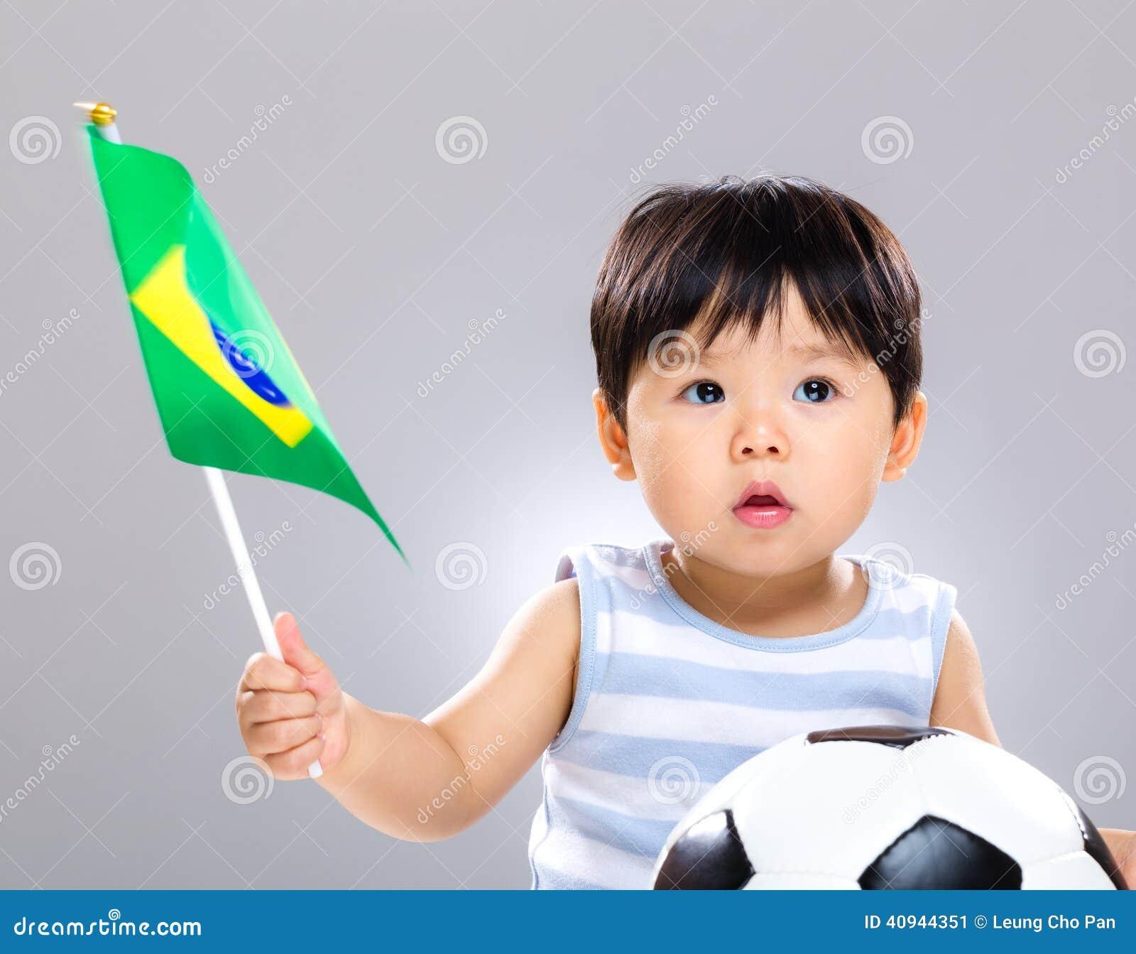 Filho do bebê que guarda a bola de futebol do amd da bandeira