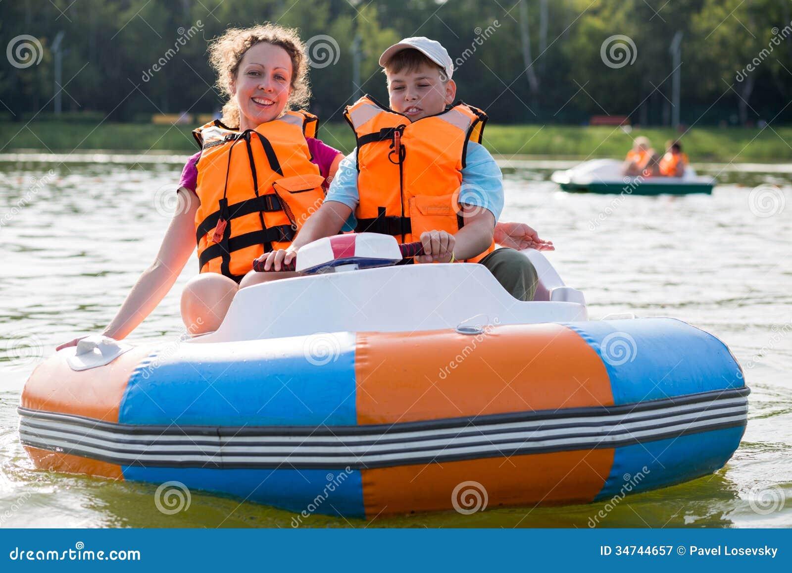 Filho e mãe nos revestimentos de vida que flutuam abaixo do rio