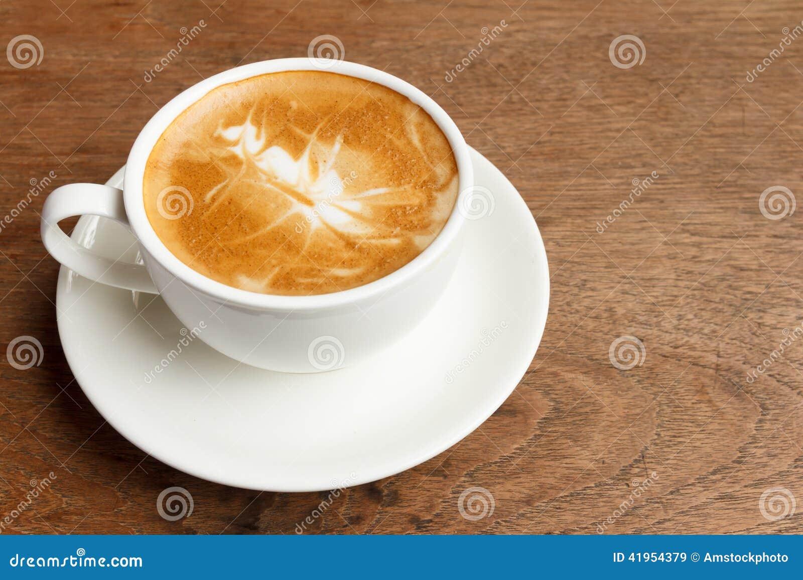 Filiżanka cappuccino na drewnianym stole