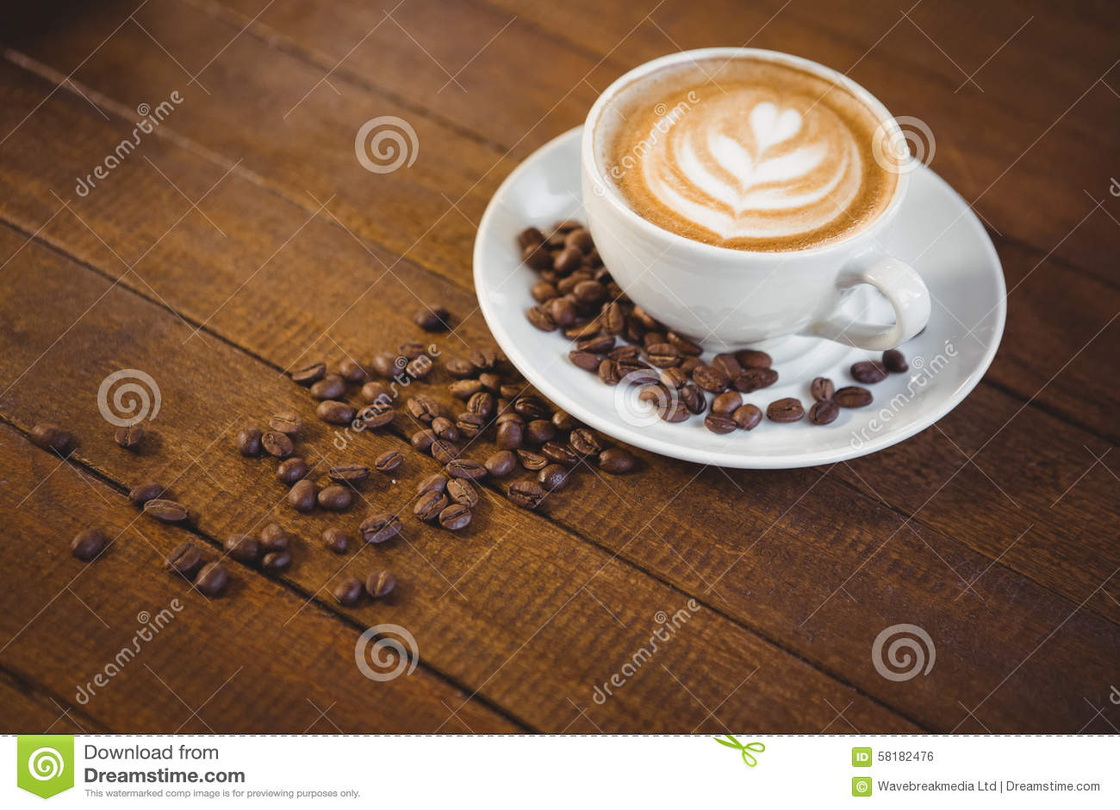 Filiżanka cappuccino z kawową sztuką i kawowymi fasolami