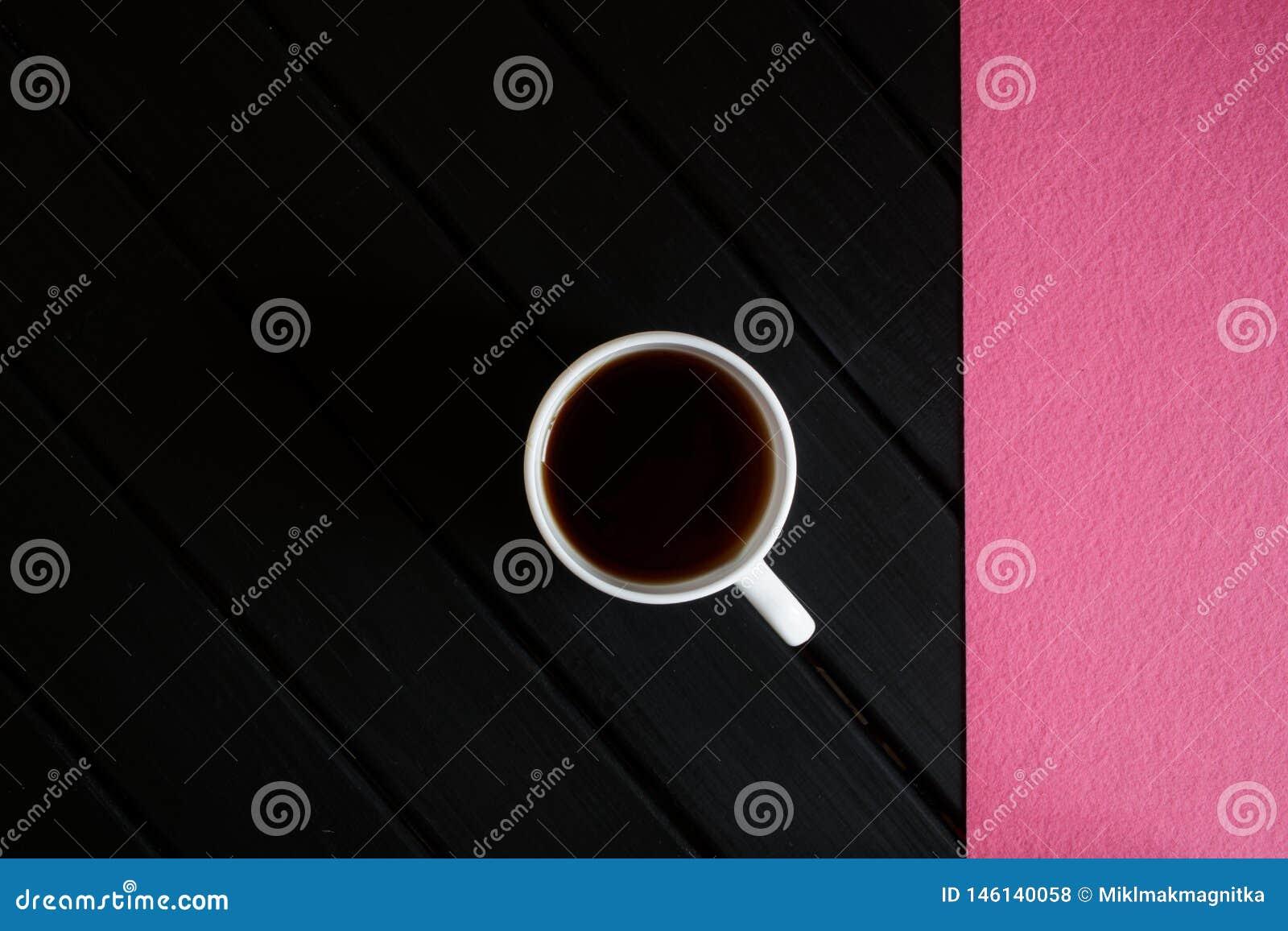 Filiżanka czarna herbata i różowa pielucha na ciemnym drewnianym stole na widok minimalista