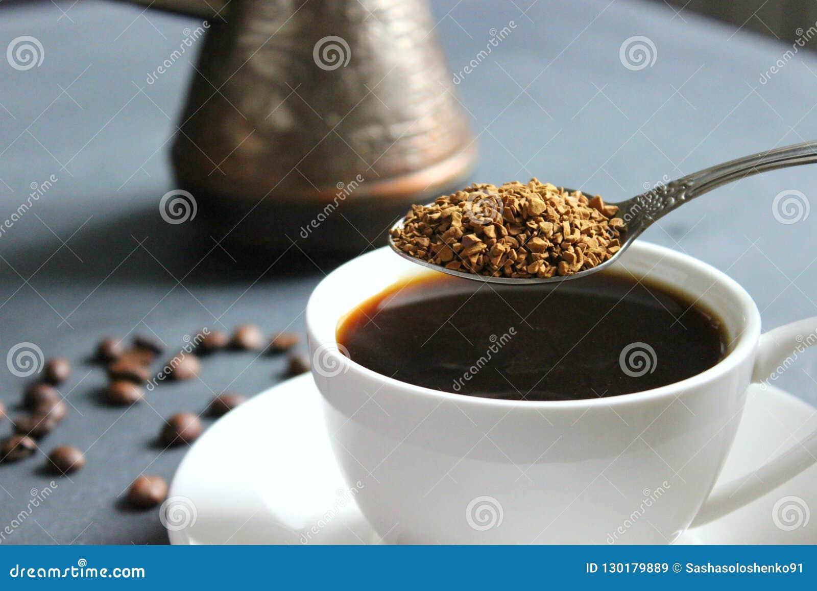 Filiżanka czarna kawa na stole, bukiet czerwone róże