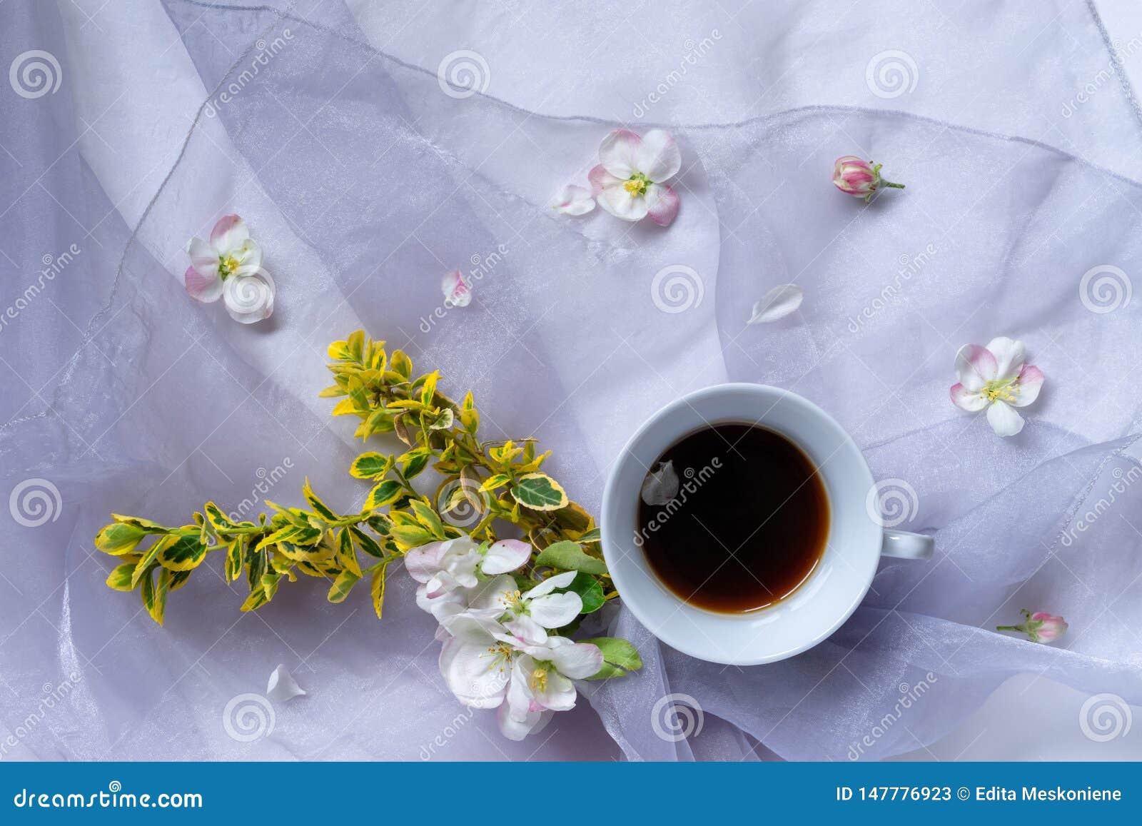 Filiżanka czarna kawa na tehe stole z bukietem