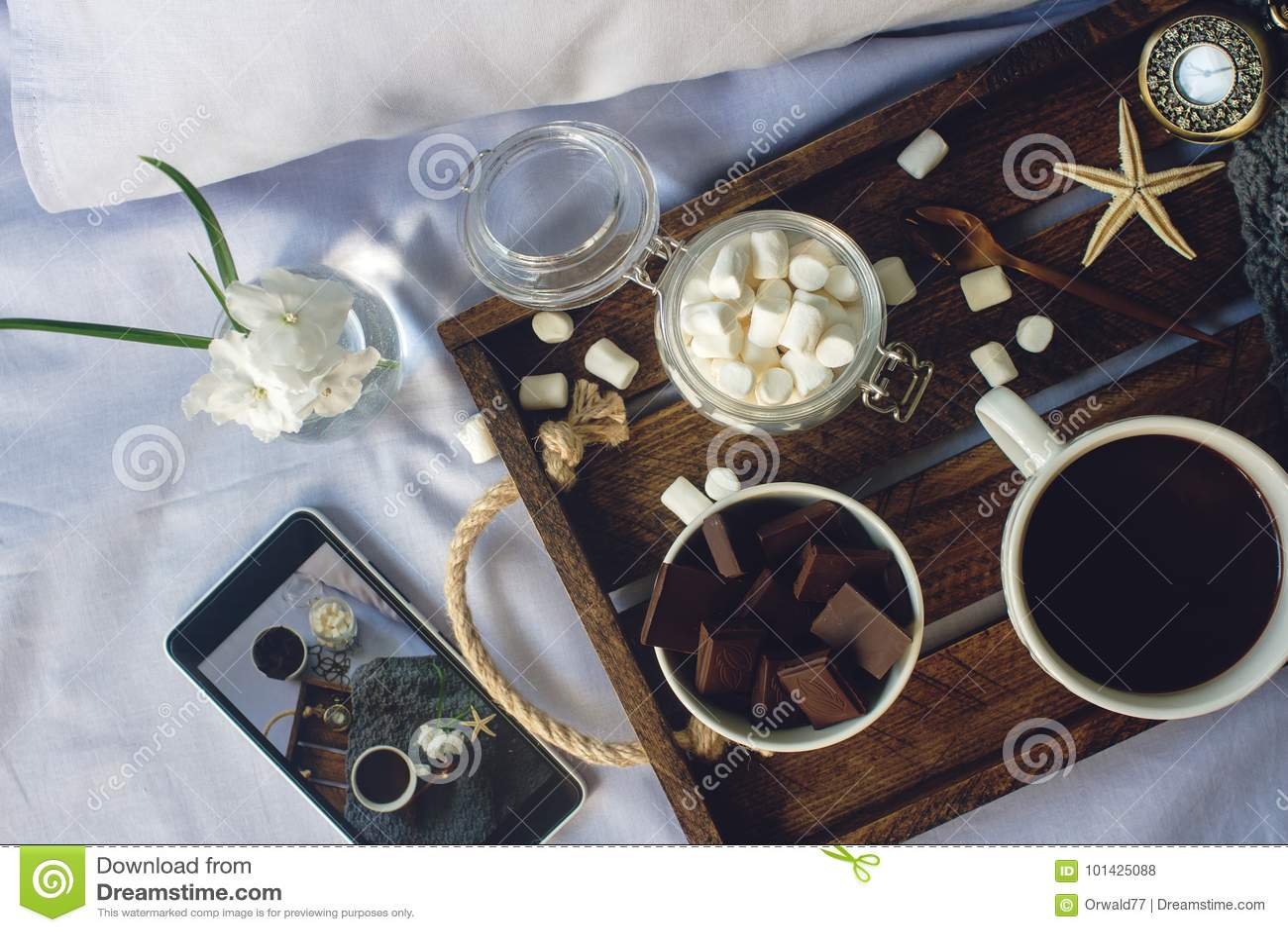 Filiżanka domowej roboty kakao z marshmallow, czekoladą, kwiatami i smartphone na nieociosanej drewnianej tacy w wygodnym łóżku,