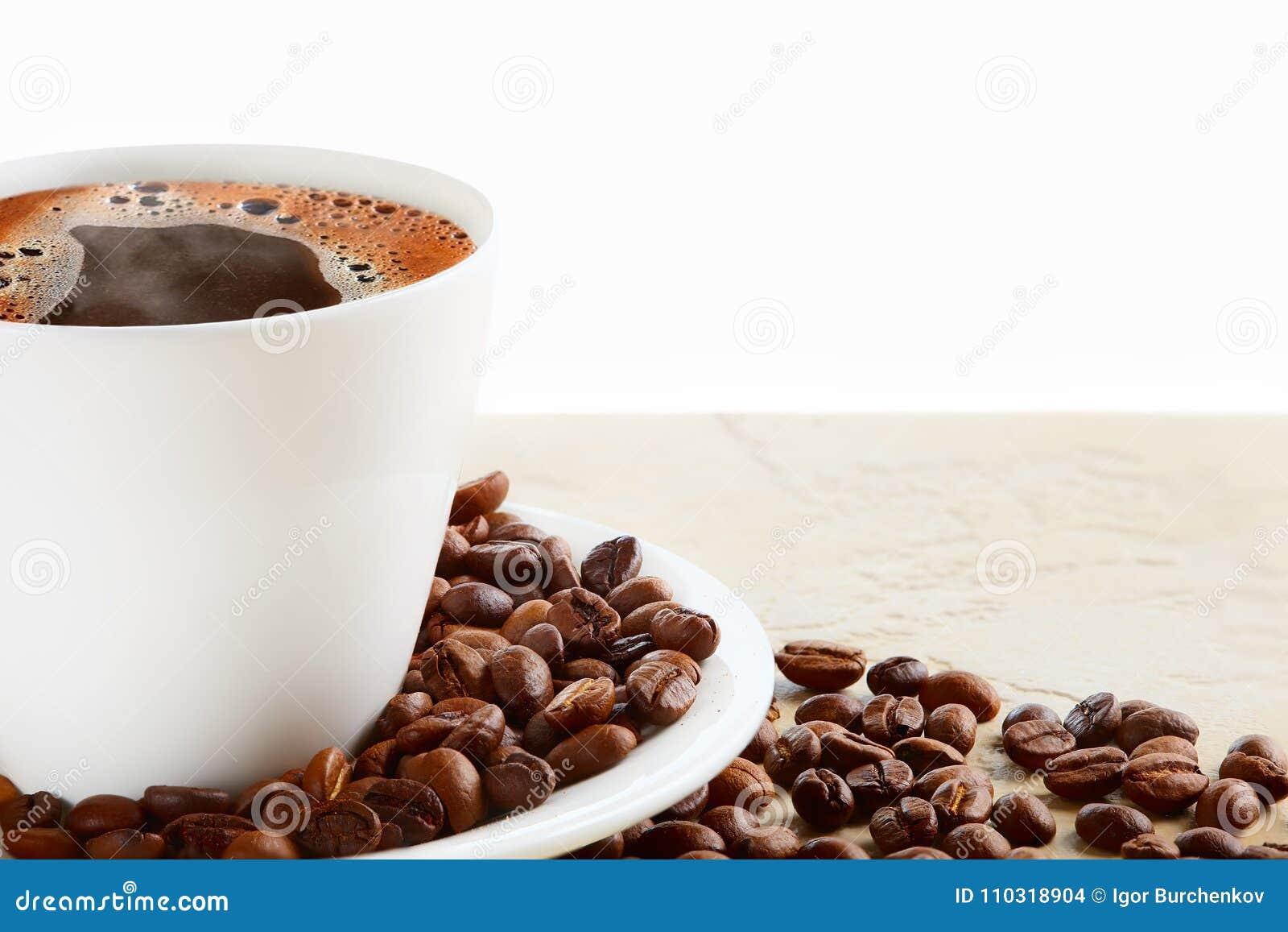 Filiżanka gorąca kawa z kawowymi fasolami na białym tle