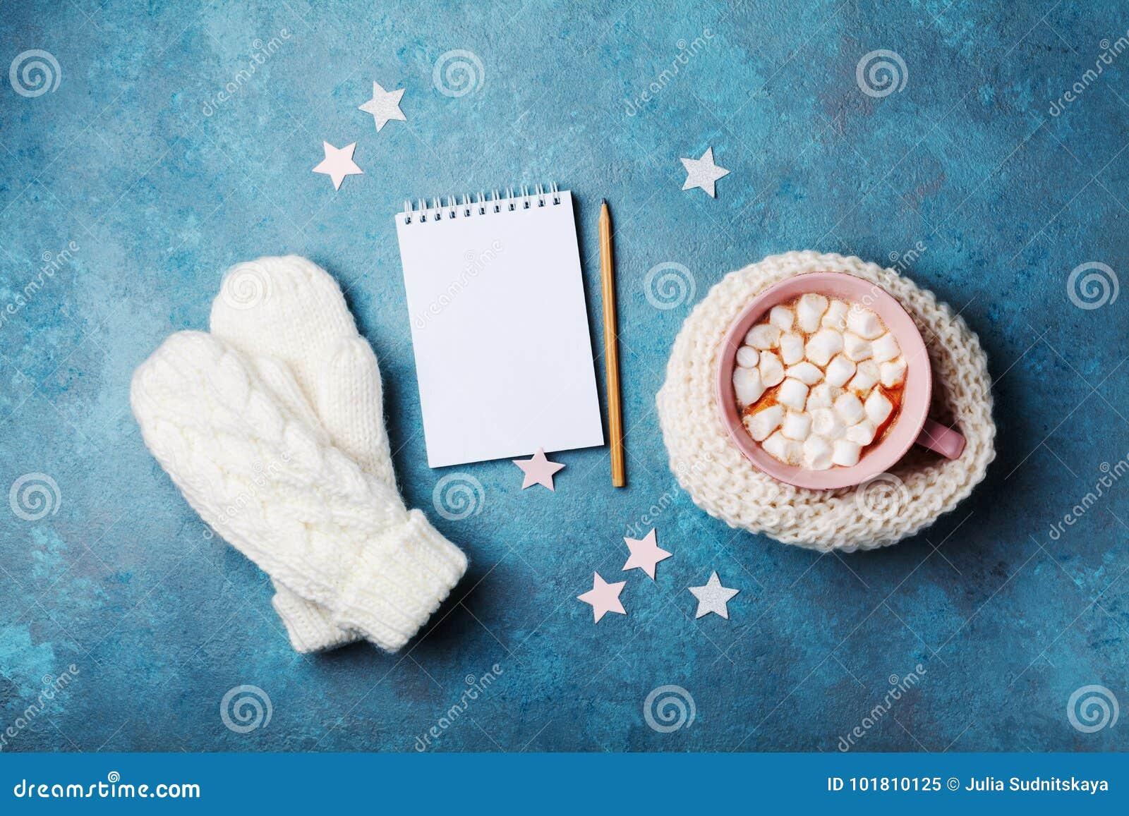 Filiżanka gorący kakao dekorował trykotowego szalika z marshmallow, mitynkami i czystym notatnikiem na turkusowym stołowym odgórn