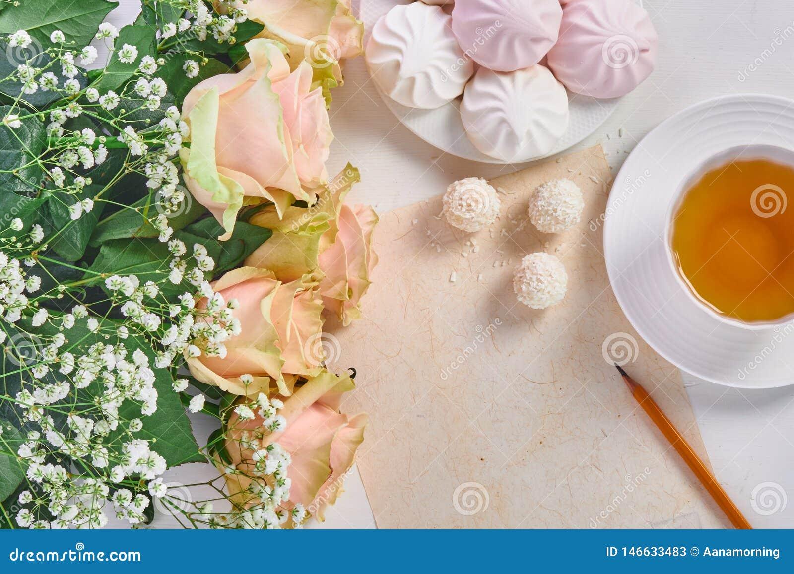 Filiżanka herbata, bukiet róże i cukierki,