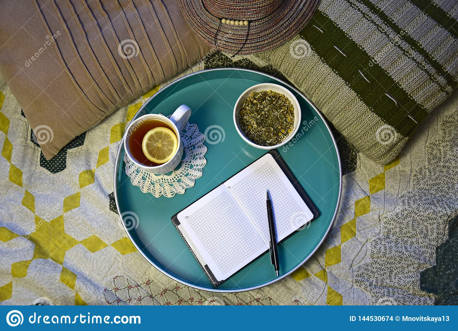 Filiżanka herbata z cytryną, naturalna ziołowa herbata i notatnik z piórem,