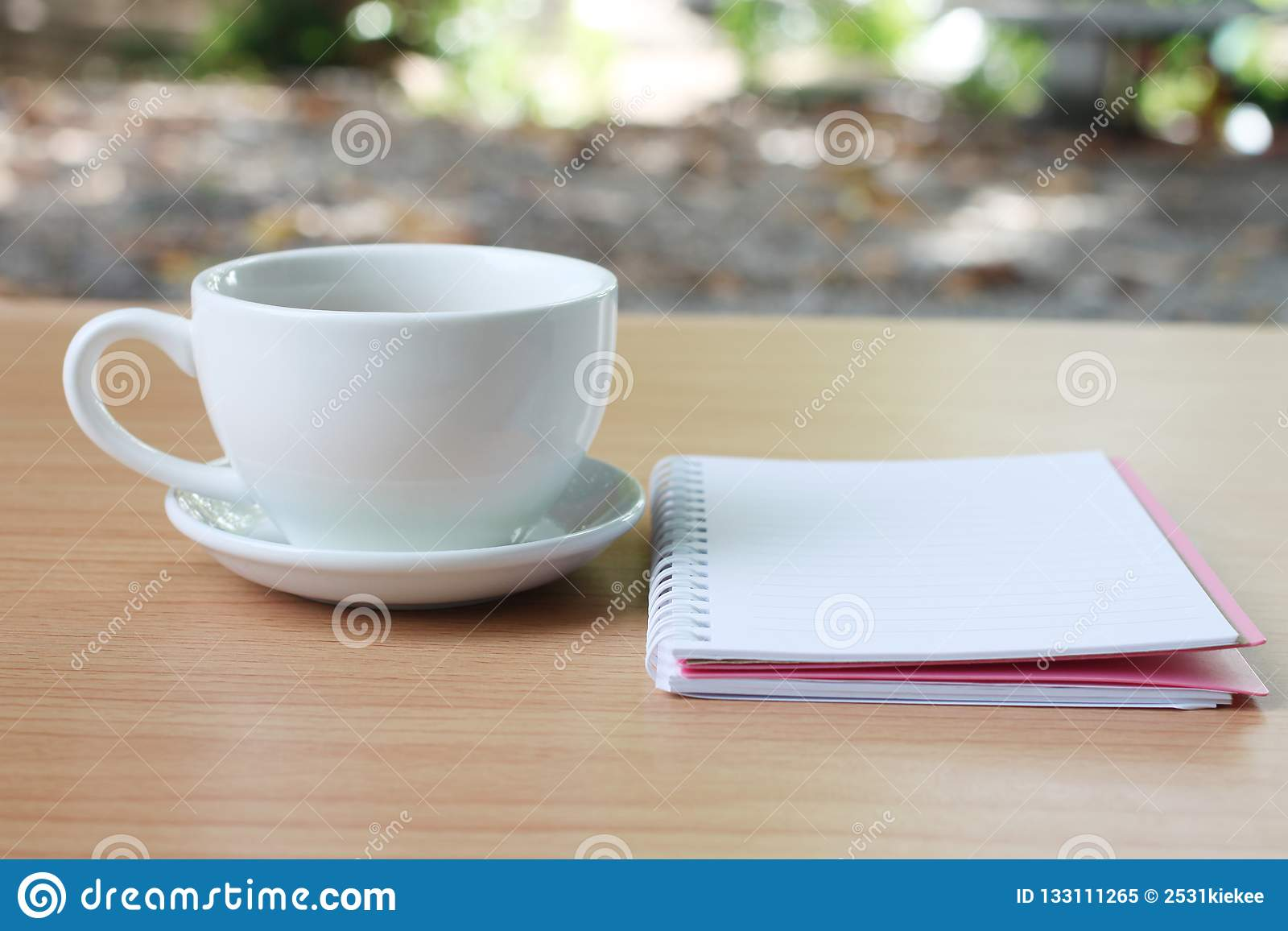 Filiżanka i notatnik umieszczamy na brązu stole drewnianym h i