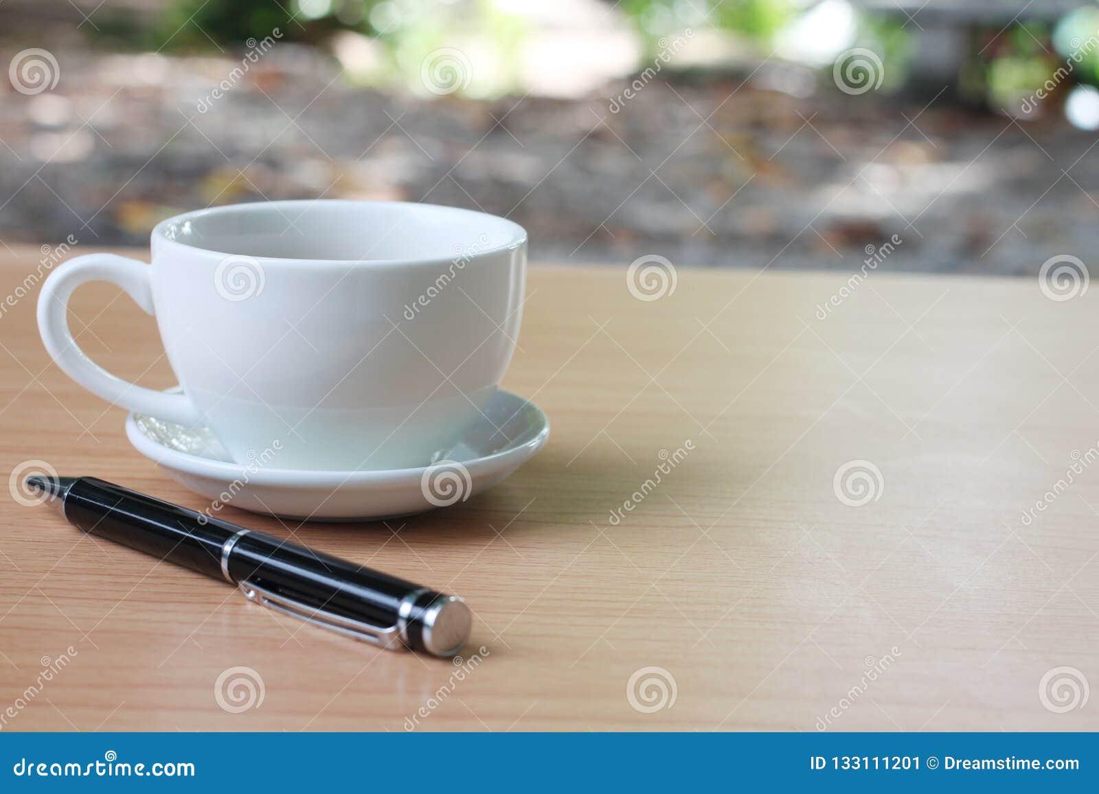 Filiżanka i pióro umieszczamy na brązu drewnianym stole i c