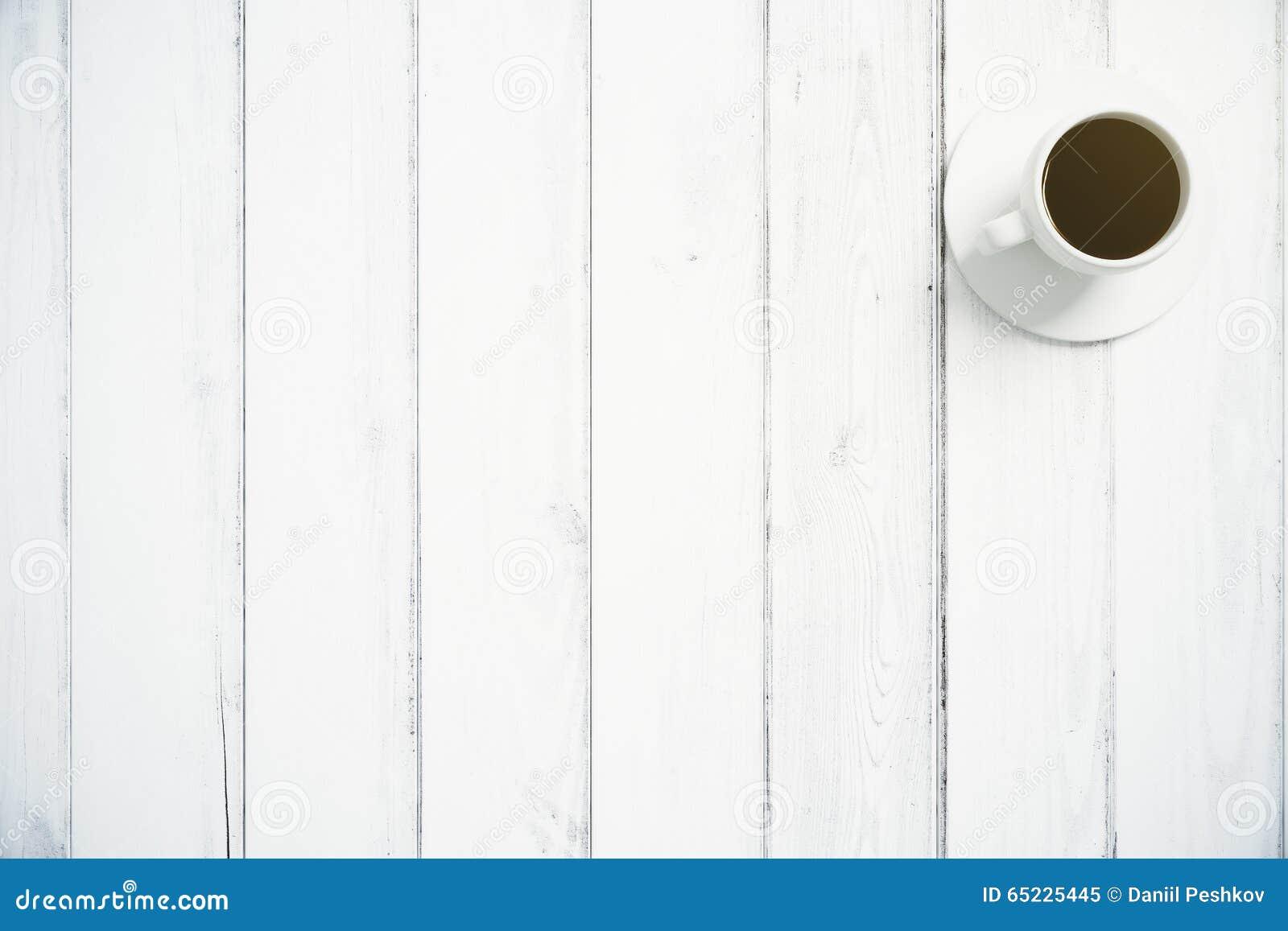 Filiżanka kawy na białej drewnianej podłoga