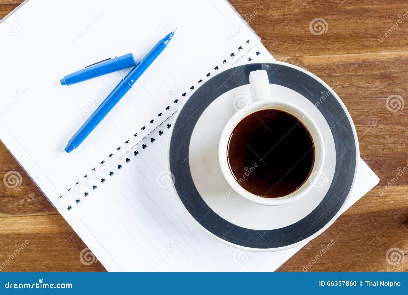 Filiżanka kawy nad notatnikiem na drewnianym stole