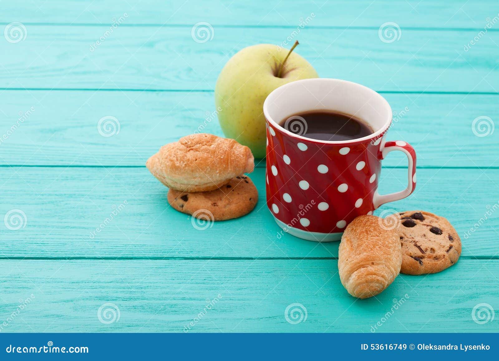 Filiżanka kawy z ciastkami, czerwone róże na błękicie