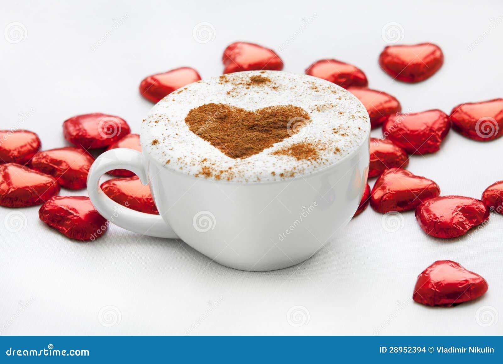 Filiżanka kawy z kierowym symbolem wokoło i cukierkiem.