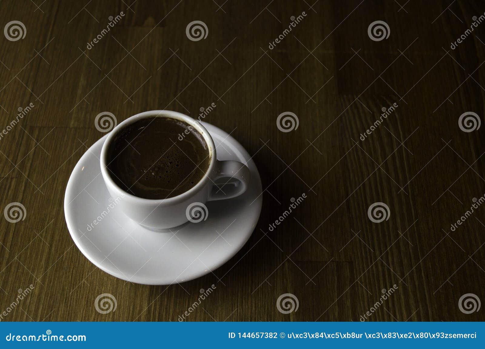 Filiżanka kawy z mlekiem i brązu stołem