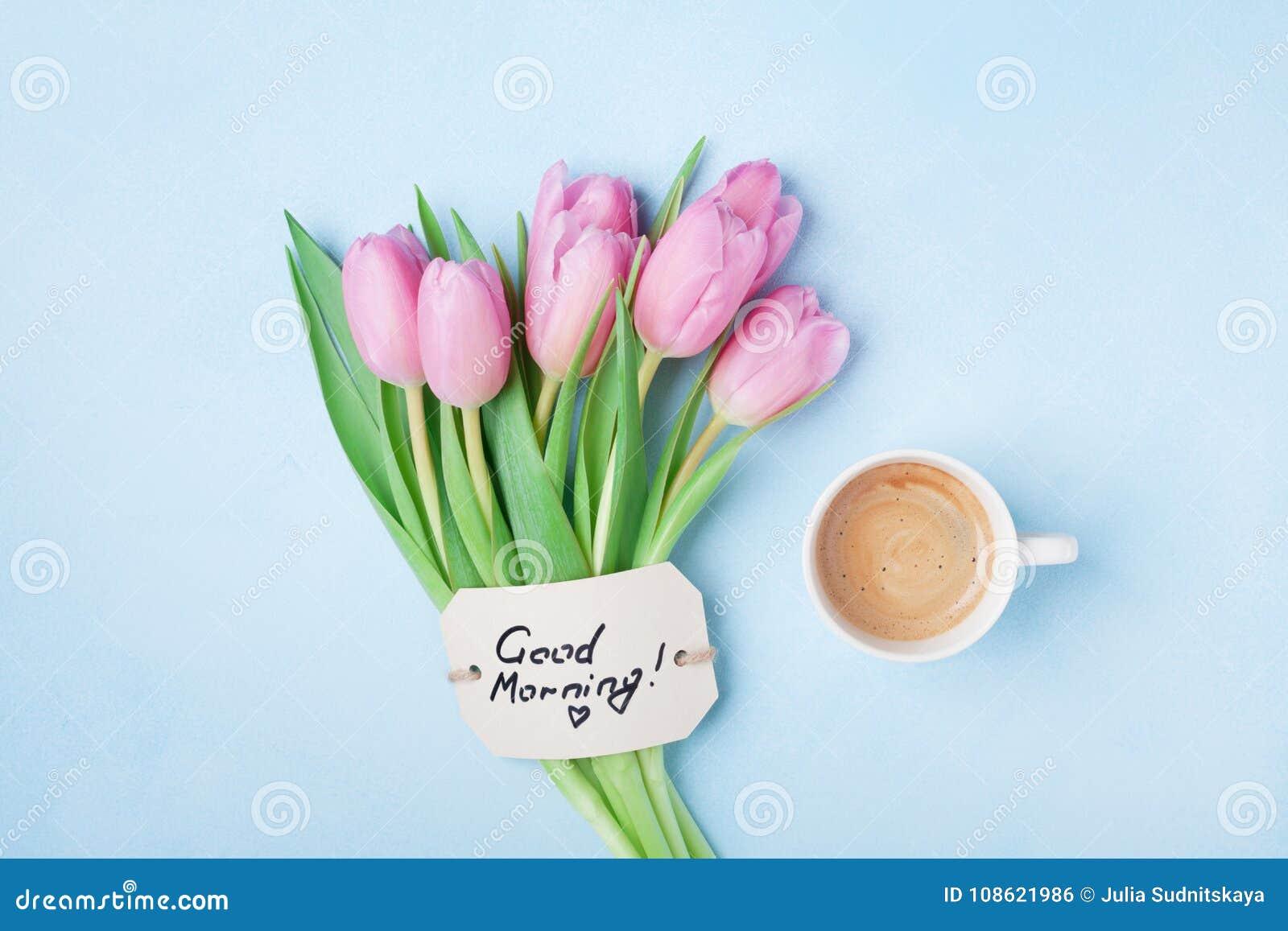 Filiżanka, różowi tulipanów kwiaty i nutowy dzień dobry na błękitnym stołowym odgórnym widoku, Piękny śniadanie na matek lub kobi