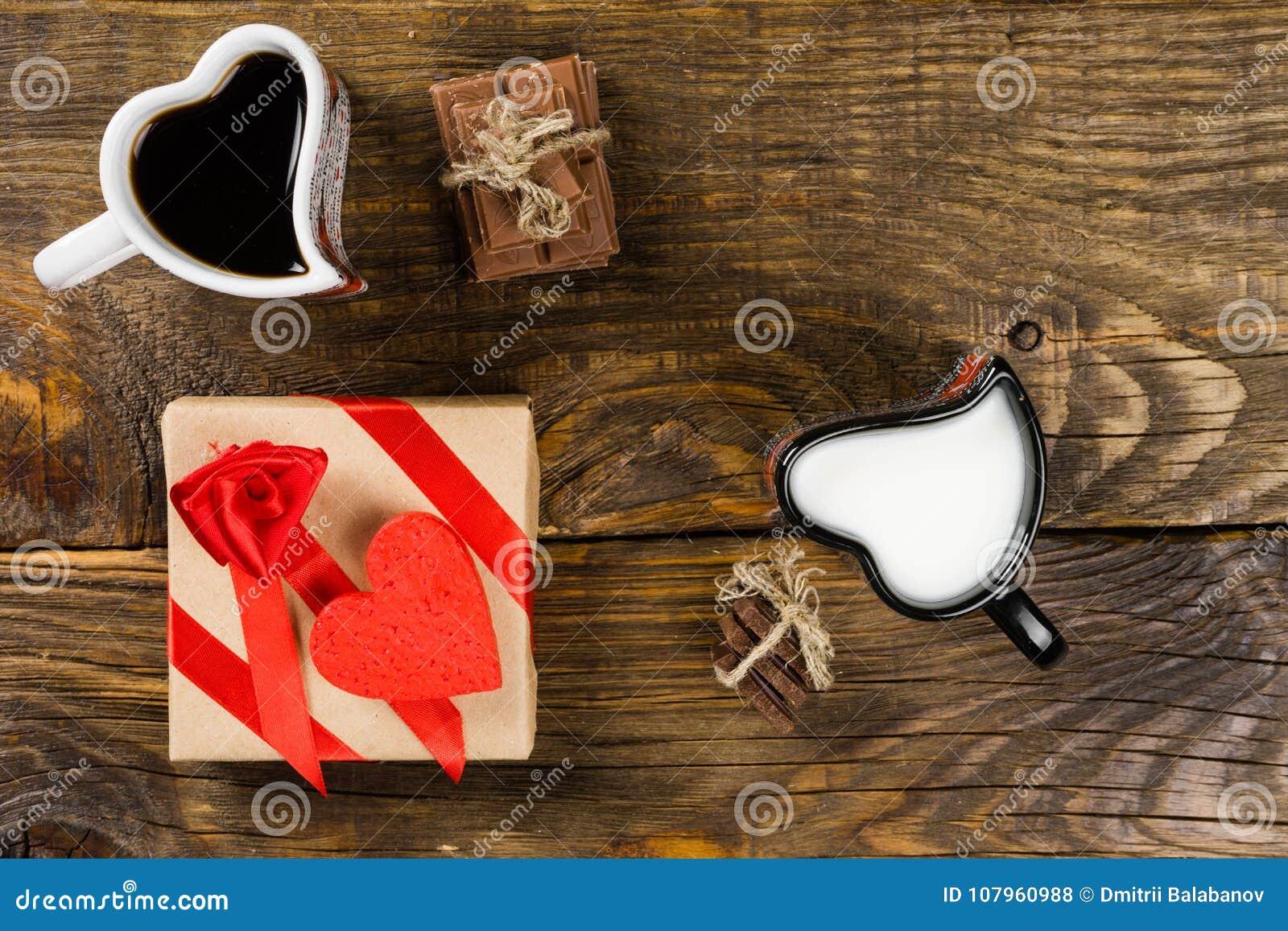 Filiżanka w formie serc, jeden nalewał kawę siekająca czekoladowa dratwa wiążąca wokoło dekoracyjnego serca w inny dojnym, następ