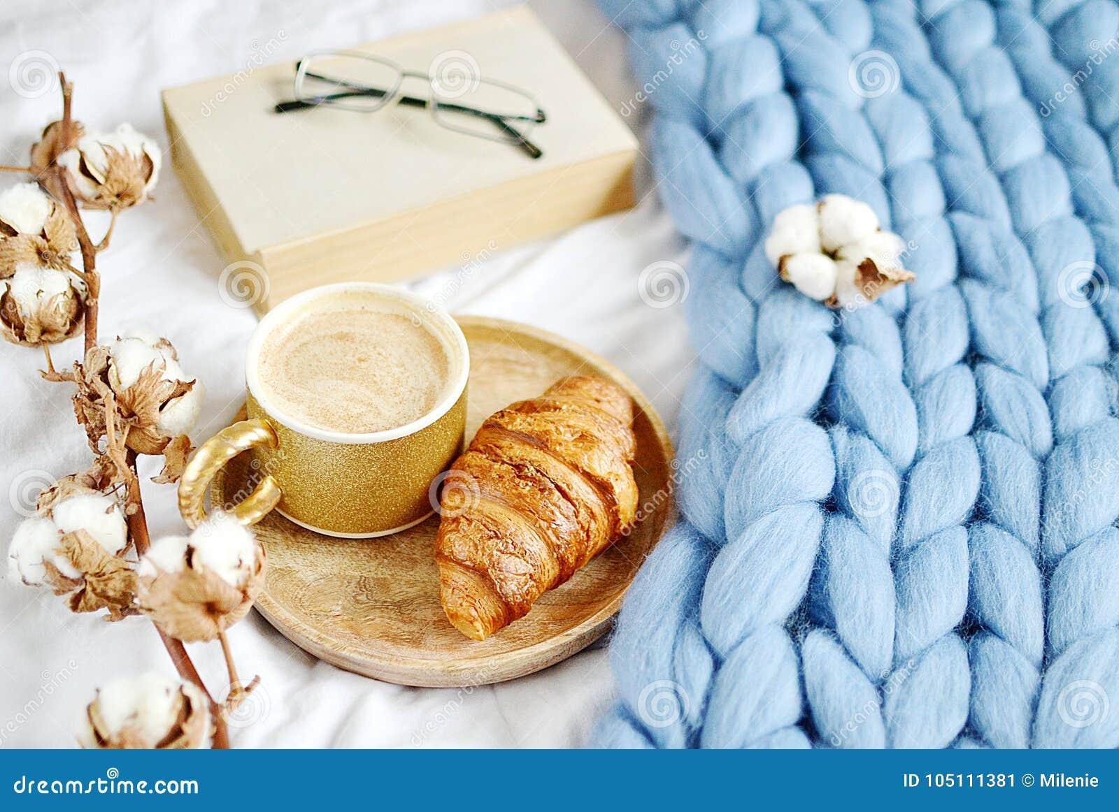 Filiżanka z cappuccino, croissant, błękitna pastelowa gigantyczna szkocka krata