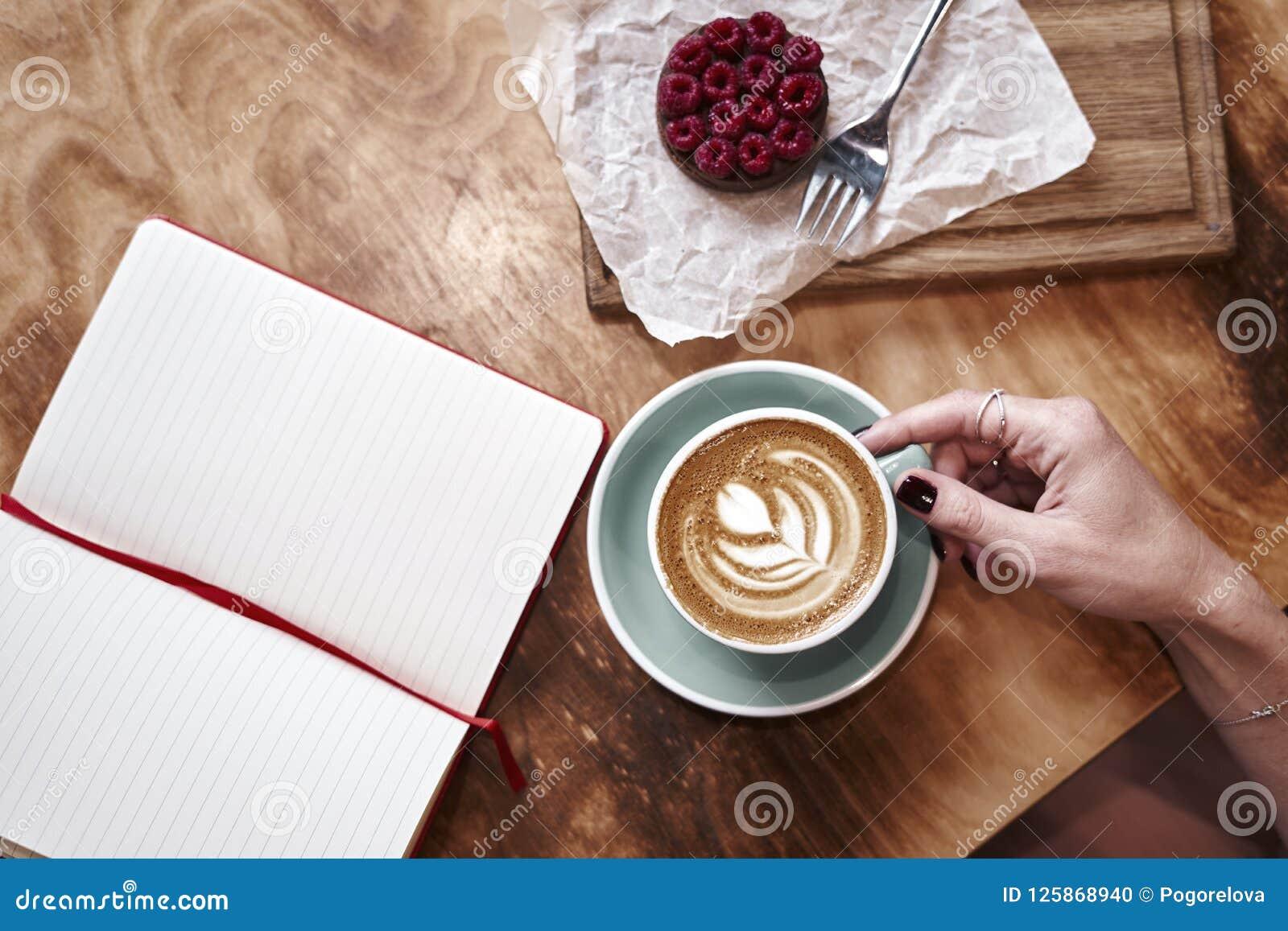 Filiżanki kawy latte na drewnianym stole lub tło w kobiet rękach od above Mieć lunch w kawiarni zeszyt otwarte