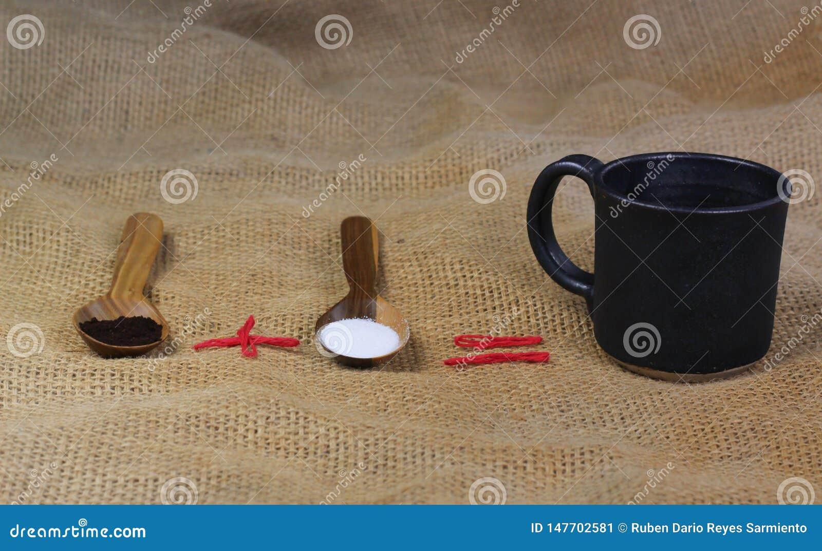 Fili?anka kawy obok drewnianych ?y?ek z kaw? i cukierem