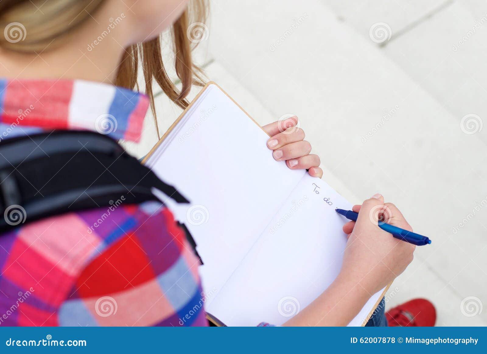 Fille écrivant a pour faire la liste dans le livre