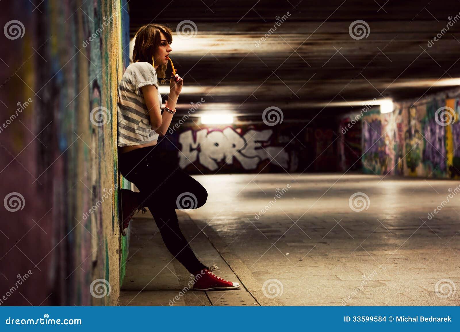 Fille élégante se tenant dans le tunnel grunge de graffiti, ville d hutte
