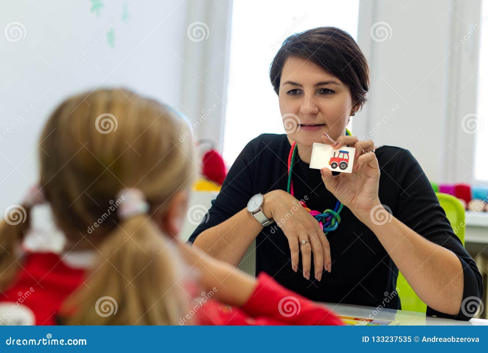 Fille élémentaire d âge en session d ergothérapie d enfant faisant des exercices espiègles avec son thérapeute
