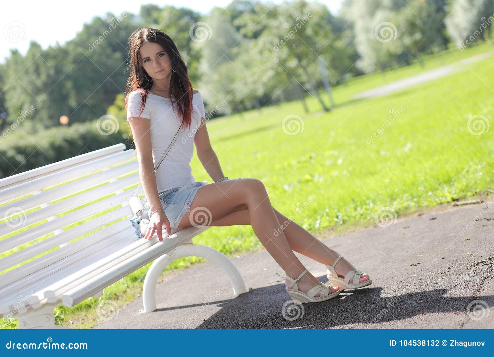Fille érotique avec la mini jupe sur l herbe verte