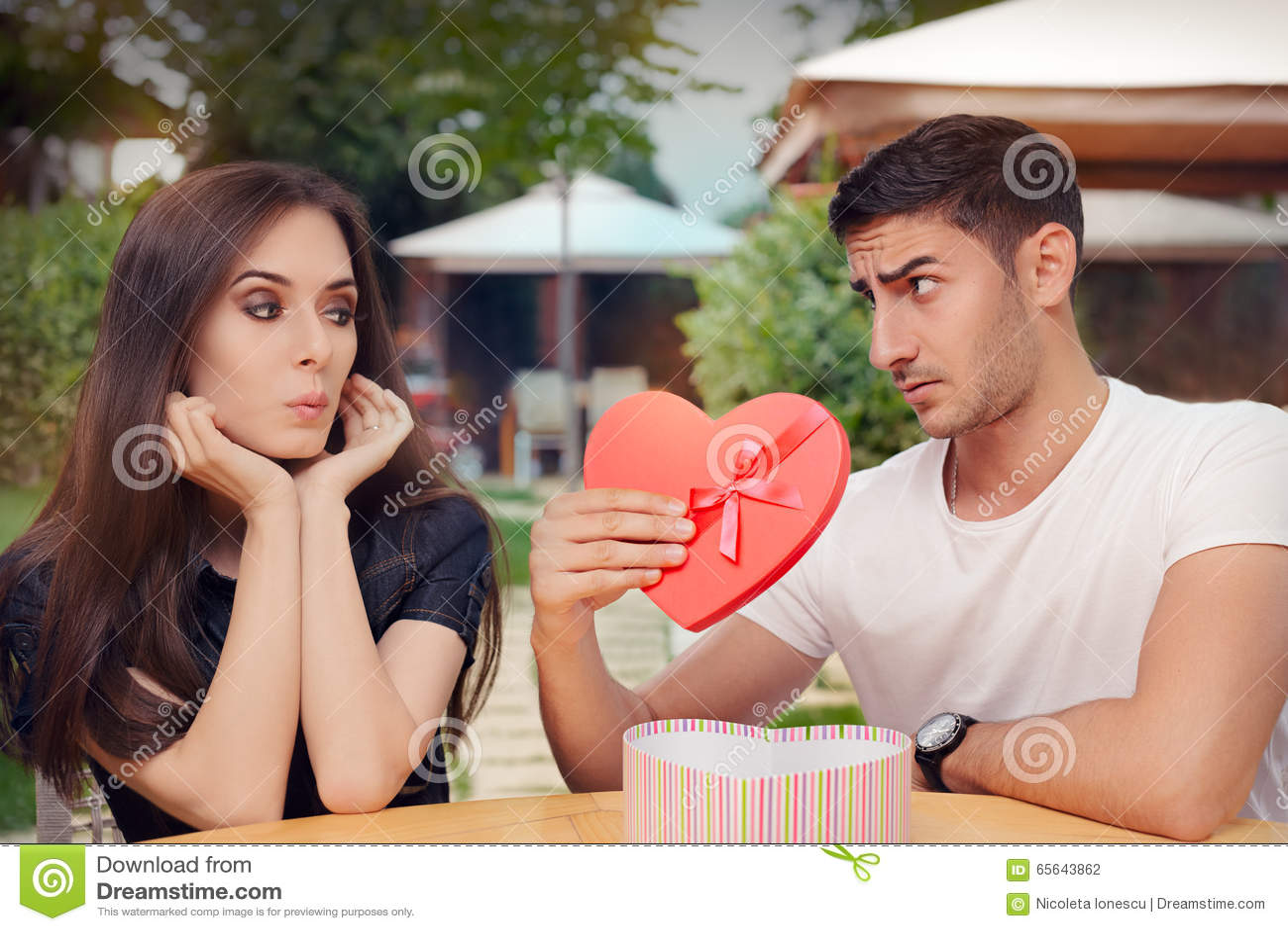 Fille étonnée recevant le cadeau en forme de coeur de son ami