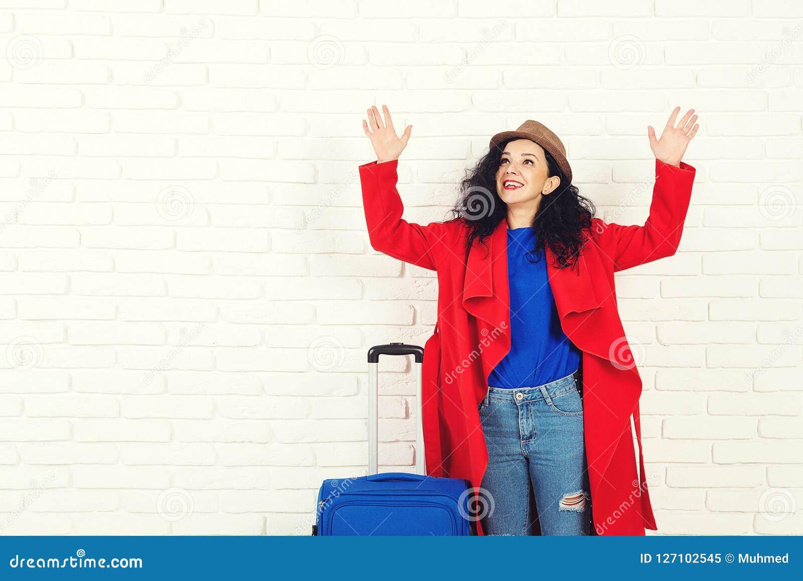 Fille étonnante avant le déplacement Jeune femme caucasienne excitée habillée dans le manteau et le chapeau rouges avec la valise