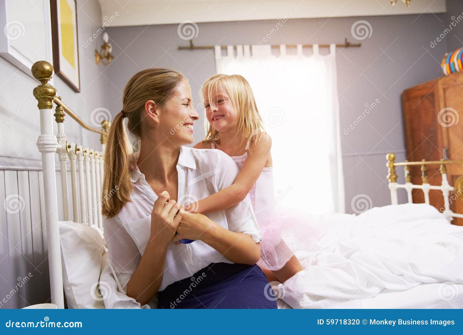 Fille étreignant la mère comme elle obtient habillée pour le travail