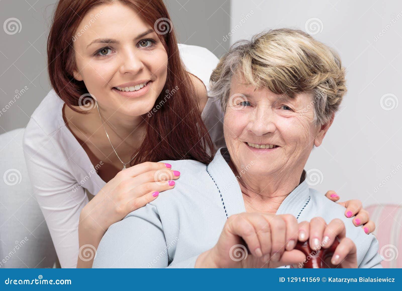 Fille étreignant la mère supérieure heureuse avec le bâton de marche au cours de la réunion