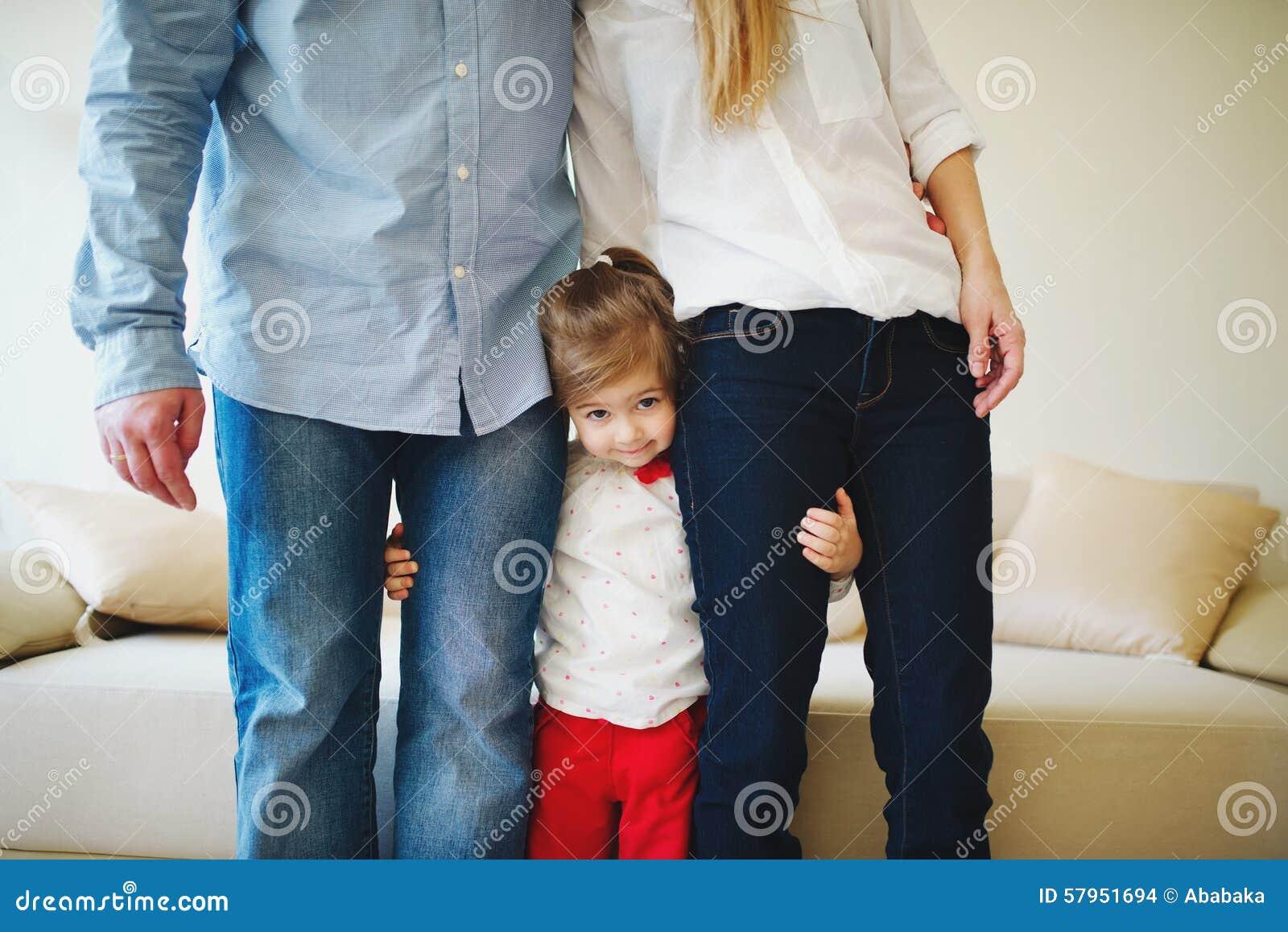Fille étreignant la maman et le papa pour des jambes
