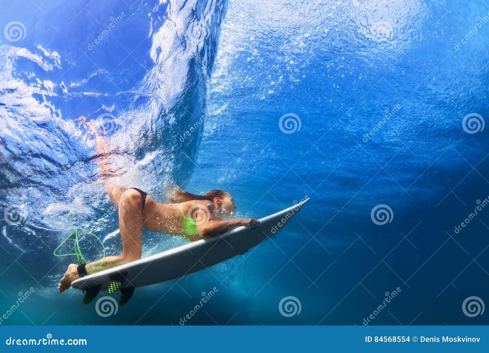 Fille active dans le bikini dans l action de piqué sur le panneau de ressac