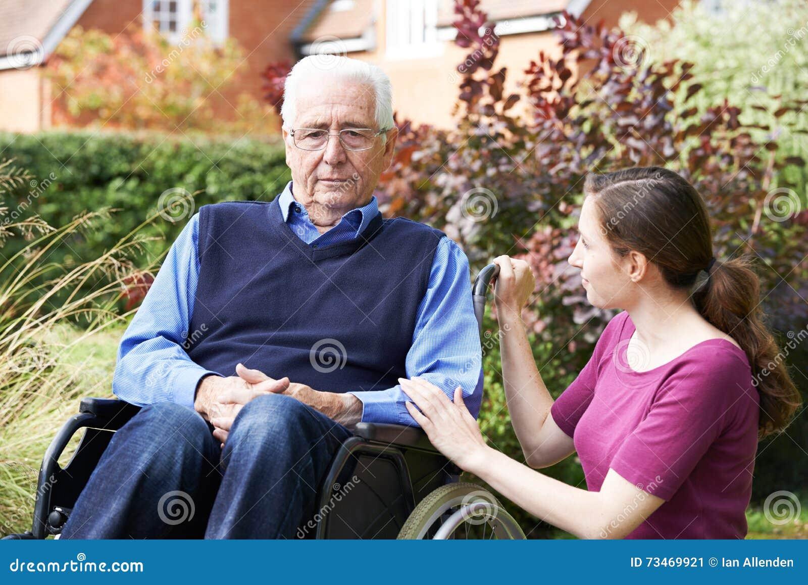 Fille adulte soulageant le père supérieur In Wheelchair