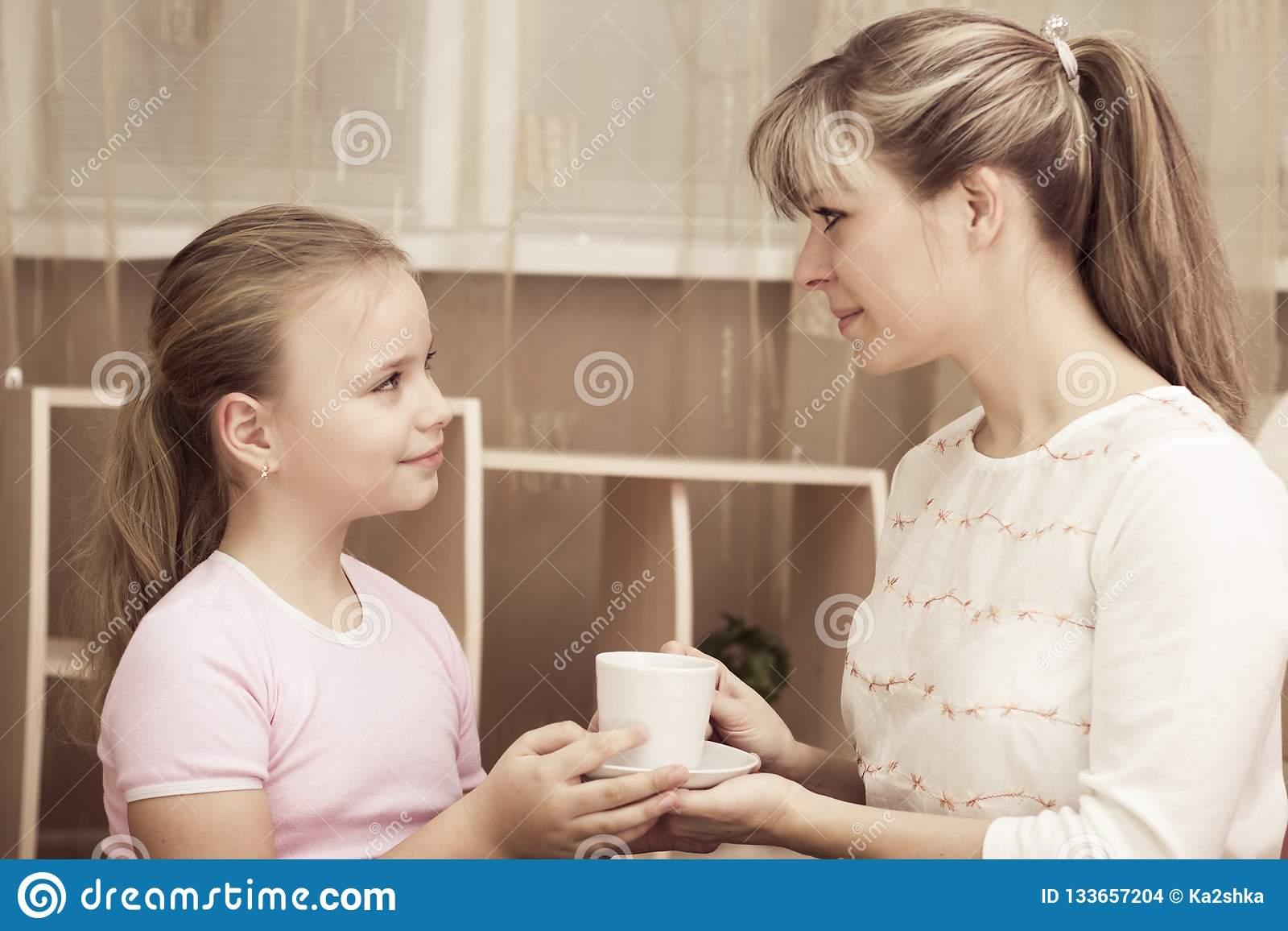 Fille affectueuse traitant sa mère dans une tasse de café