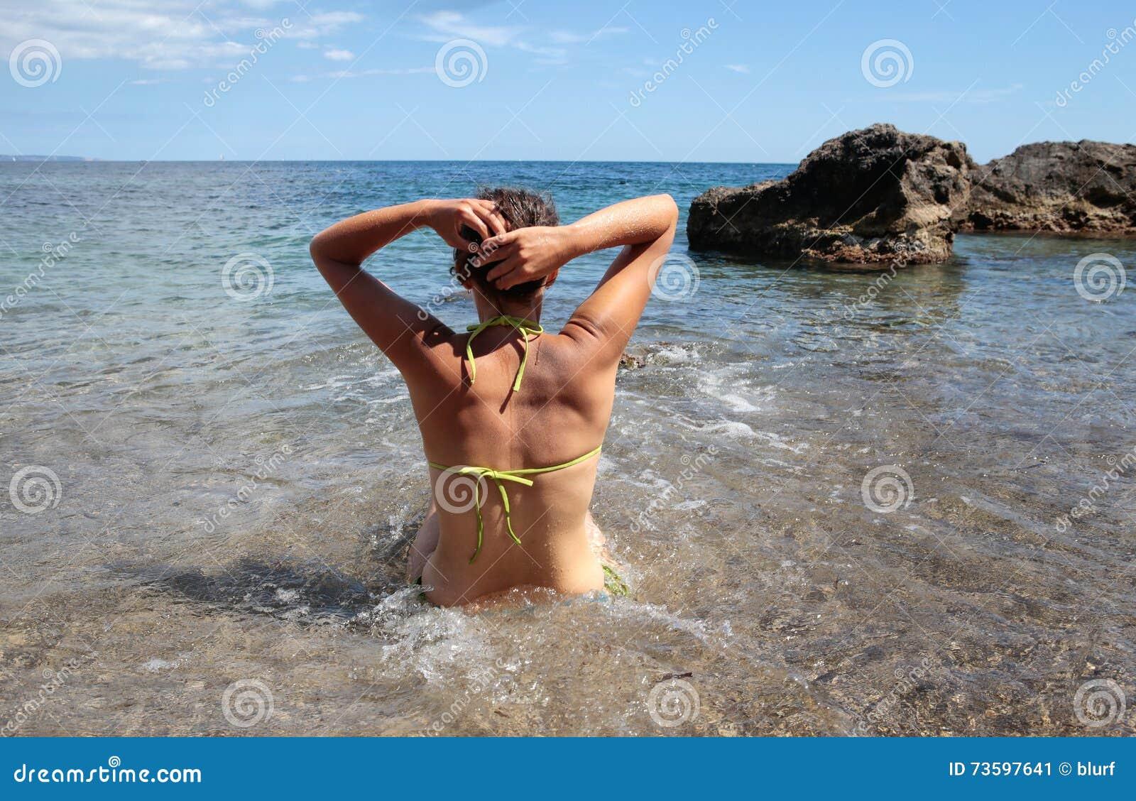 Fille ajustant ses cheveux sur la plage