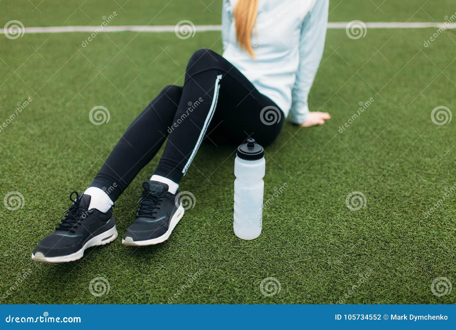 Fille après exercice, eau potable sur le terrain de football Portrait de belle fille dans les vêtements de sport