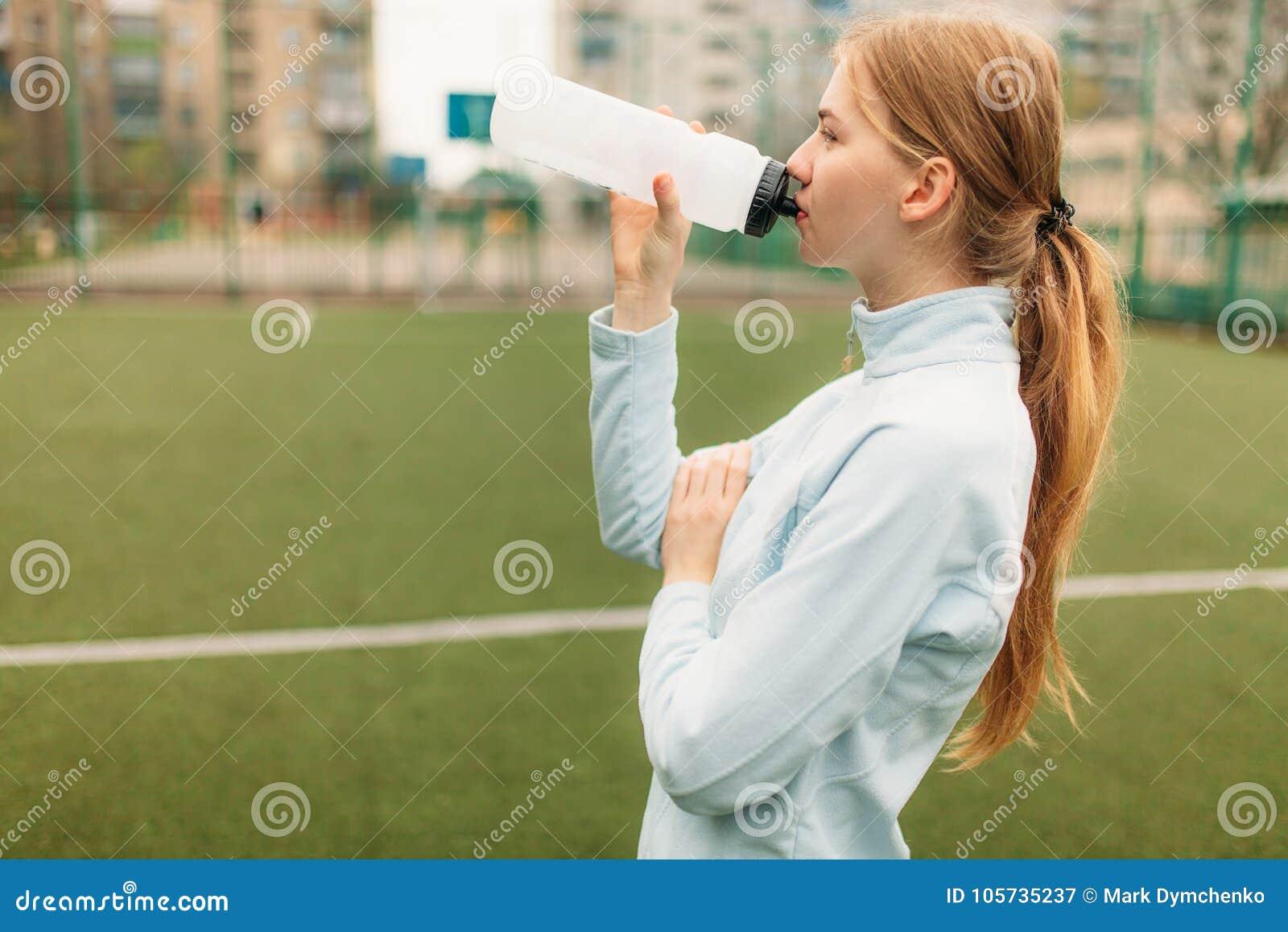 Fille après la formation, le fonctionnement ou les sports un repos dans le premier plan, une bouteille de l eau La fille travaill