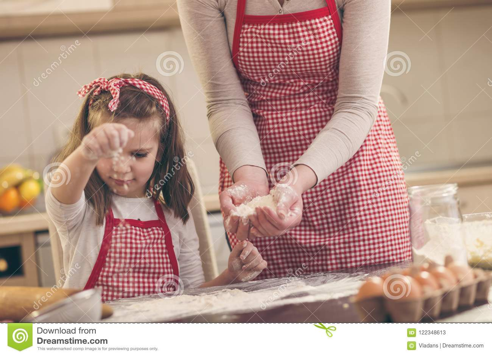 Fille arrosant la farine sur le comptoir de cuisine