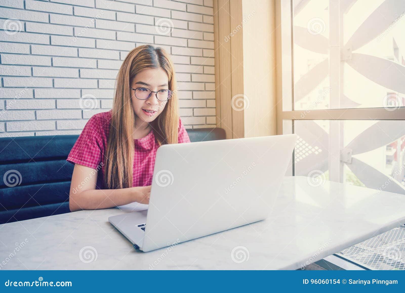 Fille asiatique à un café se reposer travaillant avec le téléphone portable