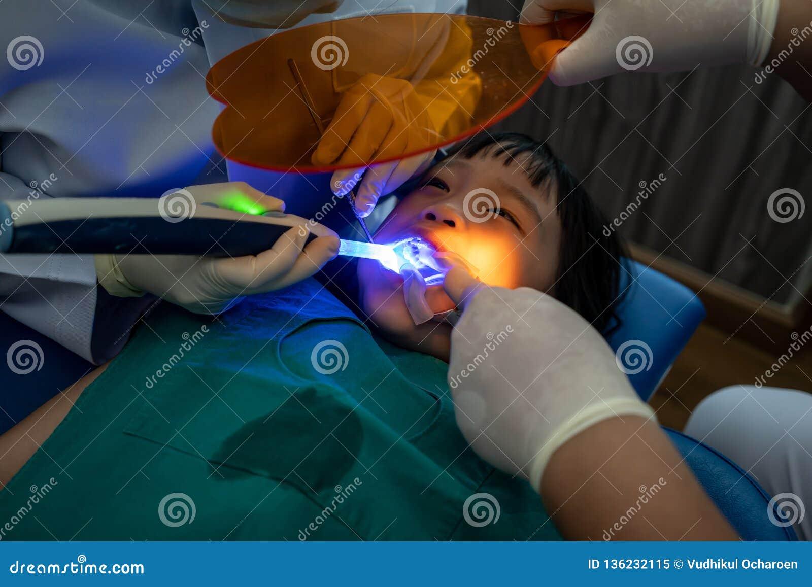 Fille asiatique atteignant le traitement remplissant dentaire la dent molaire