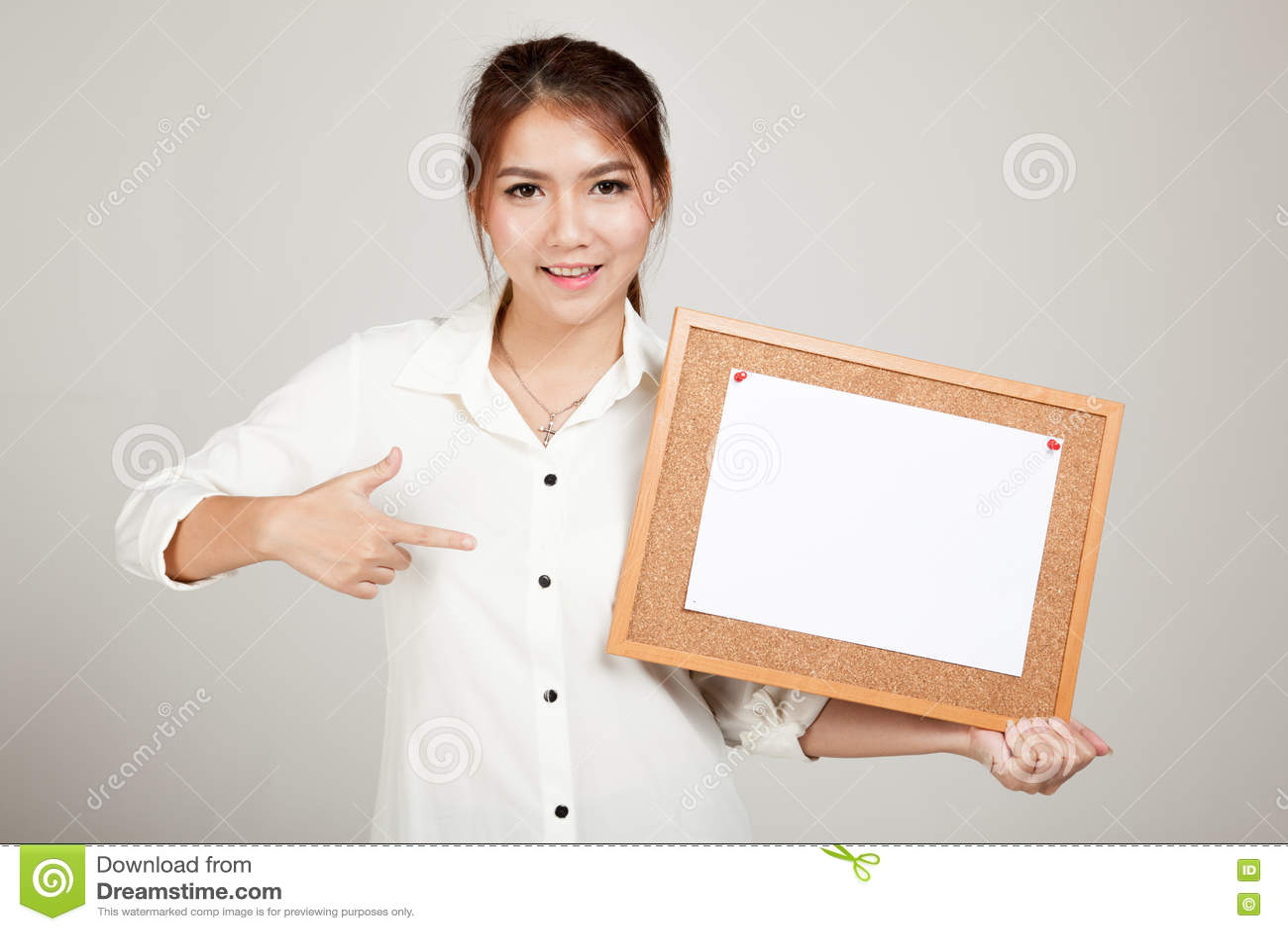 Fille asiatique avec la goupille de papier blanc sur le panneau de liège