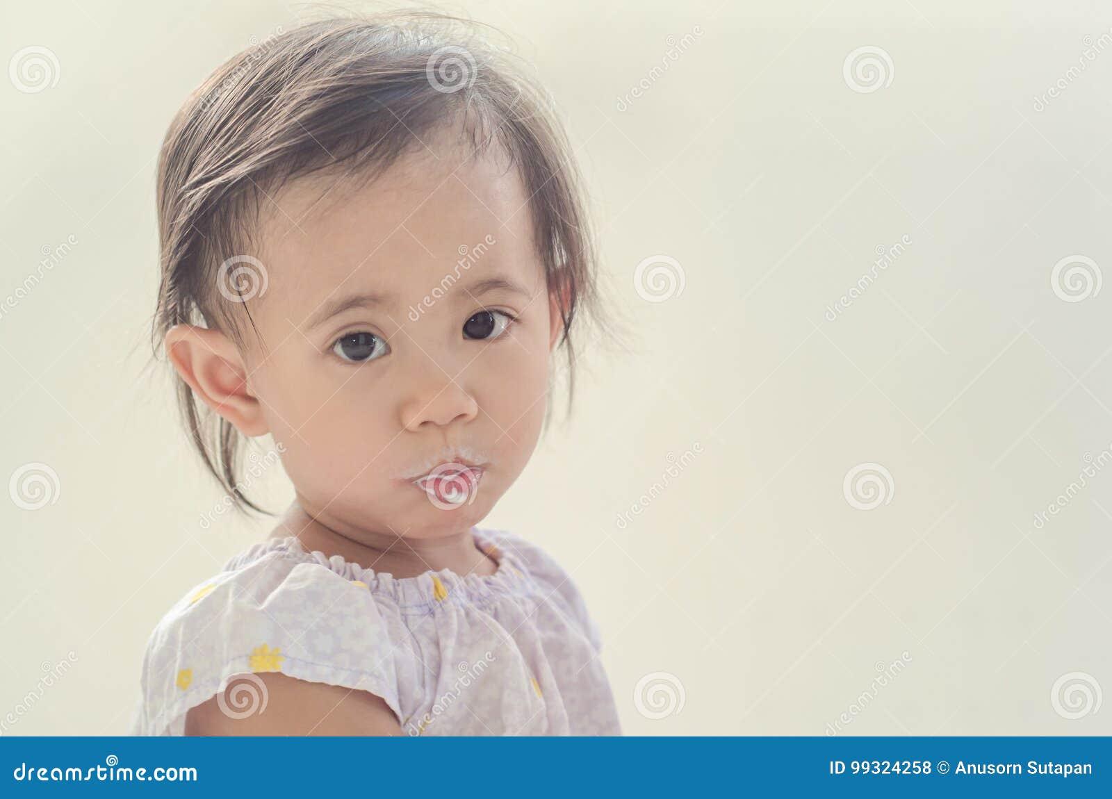 Fille asiatique d enfant en bas âge avec la bouche sale du lait