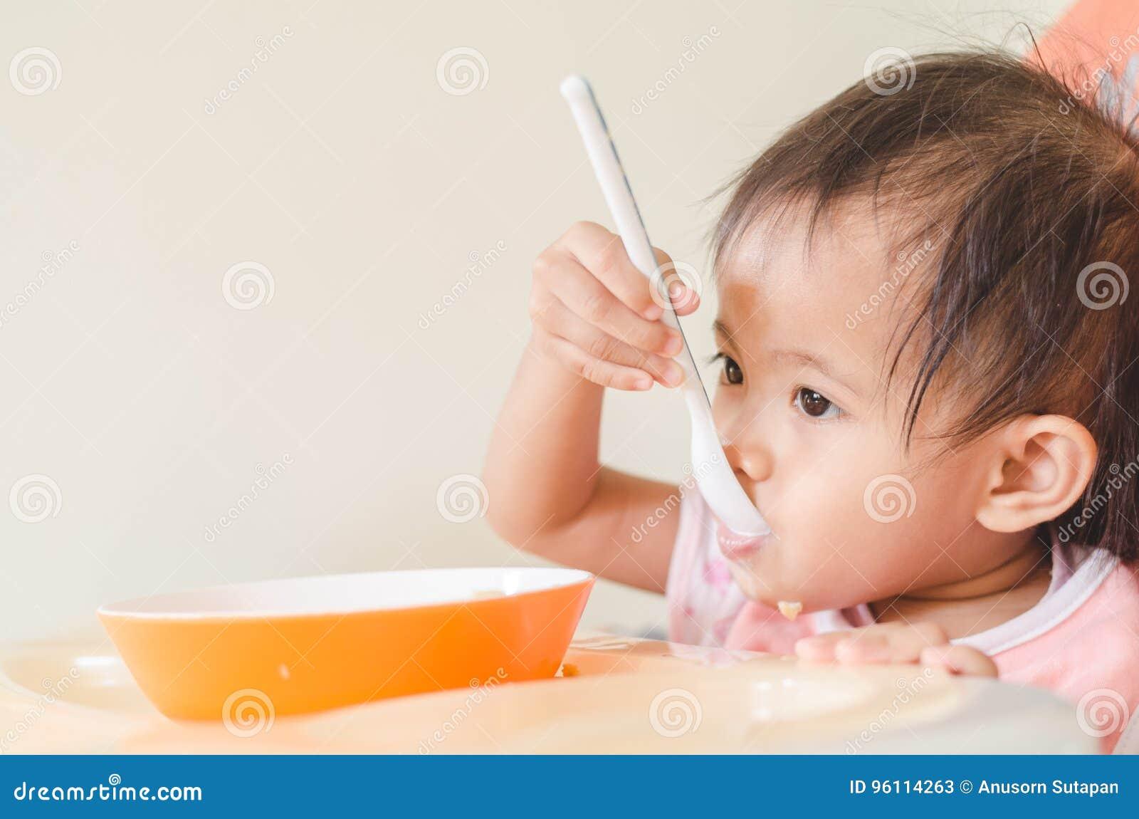Fille asiatique d enfant en bas âge mangeant des céréales avec du lait sur la chaise d arbitre au hom